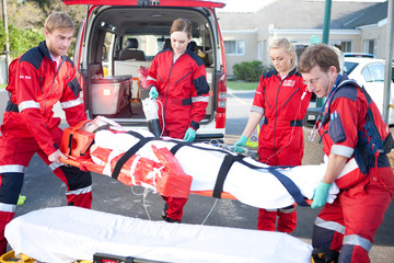Paramedics lifting woman on stretcher onto bed