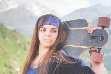 Hipster fashion girl, relaxing, holding skateboar