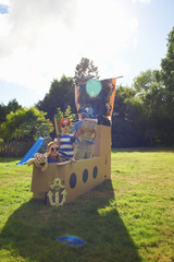 Two brothers and sister playing in garden with homemade pirate ship