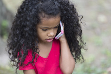 Close up of young girl listening to mobile phone in park