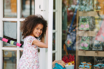 Happy young girl standing outside shop