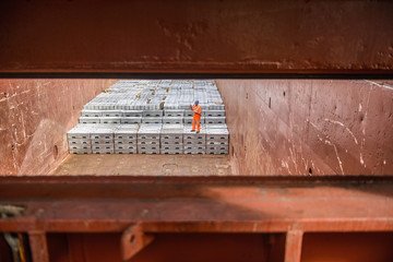 Worker checking metal ingots in ship's hold