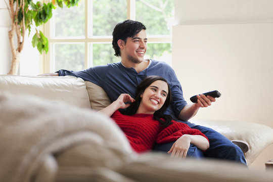 Young couple watching TV on living room sofa