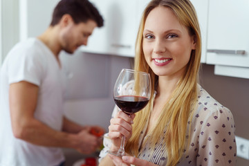 lächelnde attraktive frau mit einem glas wein in der küche