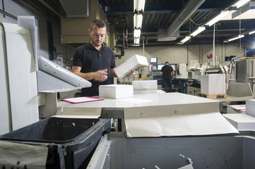 Worker preparing paper for machine in print workshop