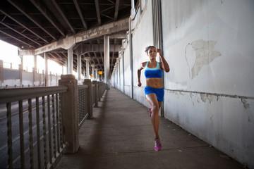 Young woman running on urban bridge