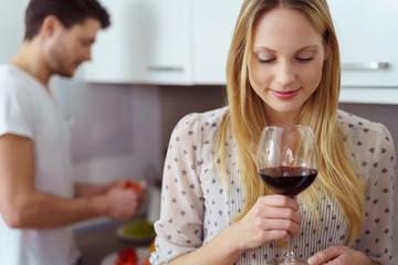 frau genießt ein glas rotwein zuhause in der küche