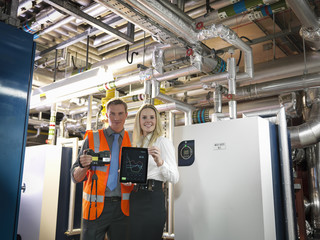 Portrait of office workers using digital tablet and camera to check efficiency of office heating in boiler room