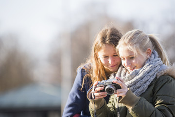 Teenage girls using camera