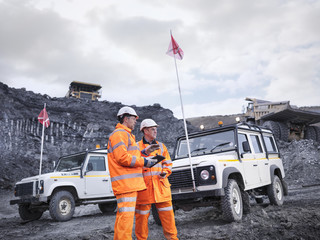 Miners with all terrain vehicles and dumper trucks in surface coal mine