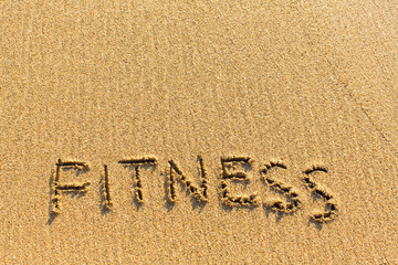 Fitness is the inscription by hand on the sand texture.