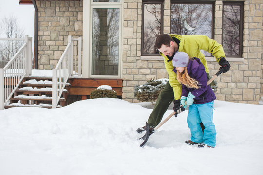 Father helping daughter to shovel snow