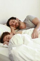 Father and young son sleeping in bed
