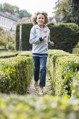 Boy running between hedges