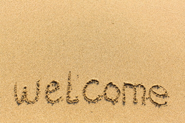 Welcome is the inscription by hand on the sand texture.