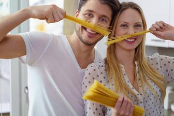 lachendes junges paar kocht spaghetti und hat spaß
