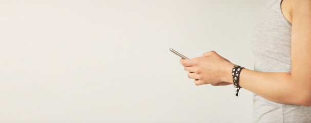Cropped shot view of a woman's hands holding mobile phone with copy space for your text message or promotional content, young female person chatting on cell telephone during work break.
