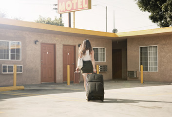 Young woman pulling wheeled suitcase outside motel, rear view