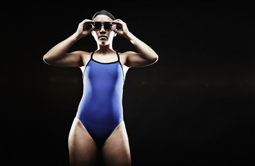 Young woman wearing blue swimsuit putting on goggles
