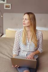 frau sitzt mit laptop auf dem bett und schaut nachdenklich zur seite