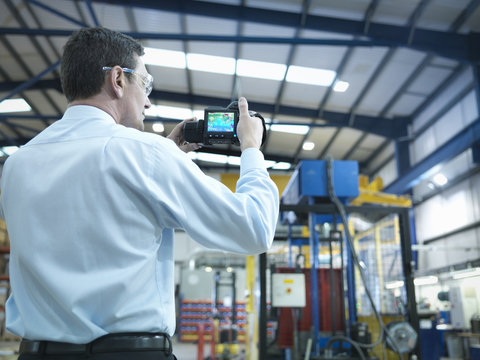 Office worker using infra red camera to check power use in factory