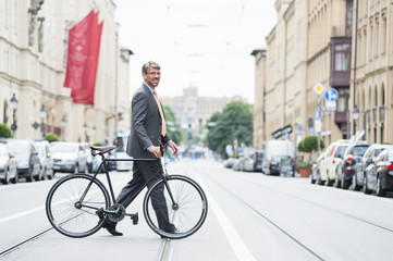 Mature businessman crossing road with bicycle