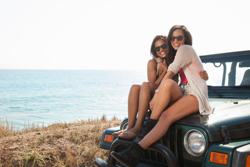 Portrait of two young women sitting on jeep hood at coast, Malibu, California, USA