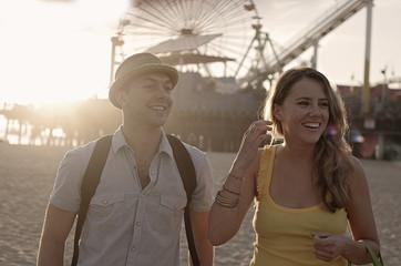Young couple laughing on beach, Santa Monica, California, USA