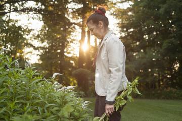 Mature woman tending garden plants