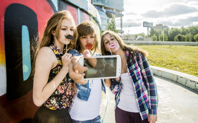 Friends taking selfie wearing fake lips and moustache, mural in background