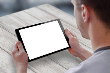 Tablet with isolated screen for mockup in man hands. Man sitting and holding tablet on table. Isolated device screen for design, interface promotion.