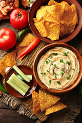 Wooden bowl of tasty hummus with chips, cucumber and parsley on table