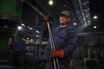Forge worker primed for action with a set of industrial tongs