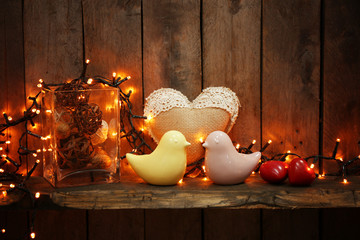 Ceramic birds and lighted garland on wooden background