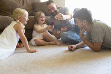 Male couple and two daughters playing on sitting room floor