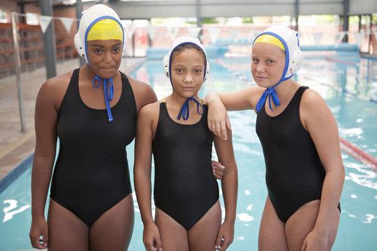 Portrait of three schoolgirl water polo players poolside