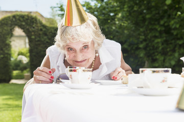 Senior woman wearing party hat looking at camera, smiling