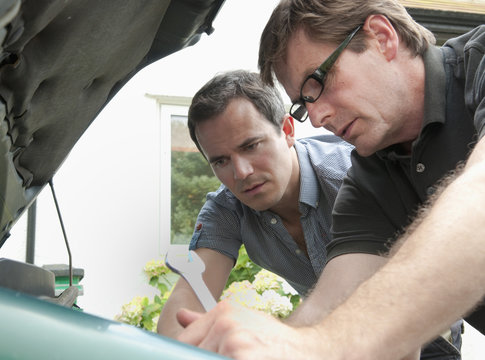 Two male adult friends checking under car hood
