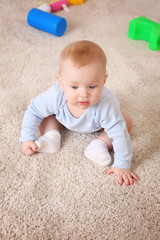 Cute baby with plastic toys on the floor, close up