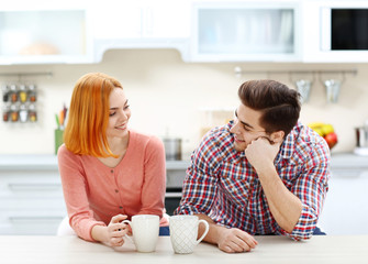 Young beautiful couple with cups of tea in the kitchen