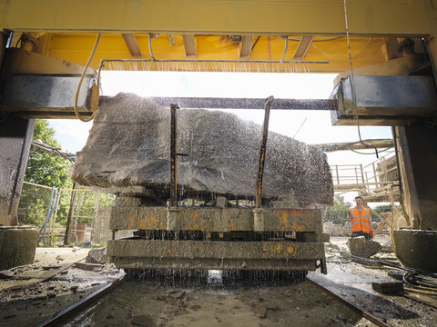Large rock being cut in stone saw in quarry
