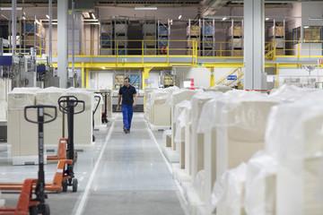 Worker walking through paper packaging factory