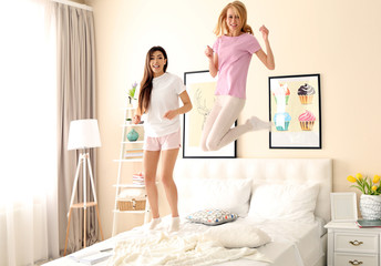 Two girls having fun together on a bed in living room