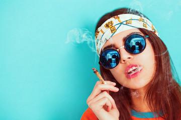 Hippie girl portrait smoking and wearing sunglasses