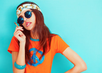 Hippie girl smoking and wearing sunglasses