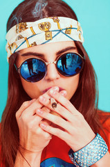 Hippie girl smoking weed and wearing sunglasses