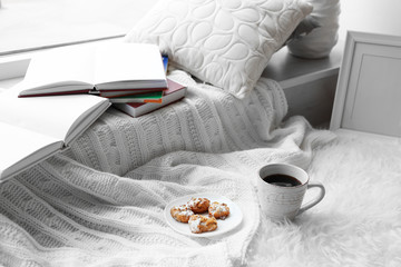 Biscuits and cup of tea on blanket indoors