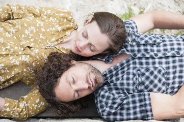 Overhead view of mid adult couple asleep on ground