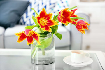 A bouquet of red tulips in a glass on white table.
