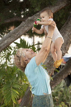 Grandmother holding baby granddaughter with rattles
